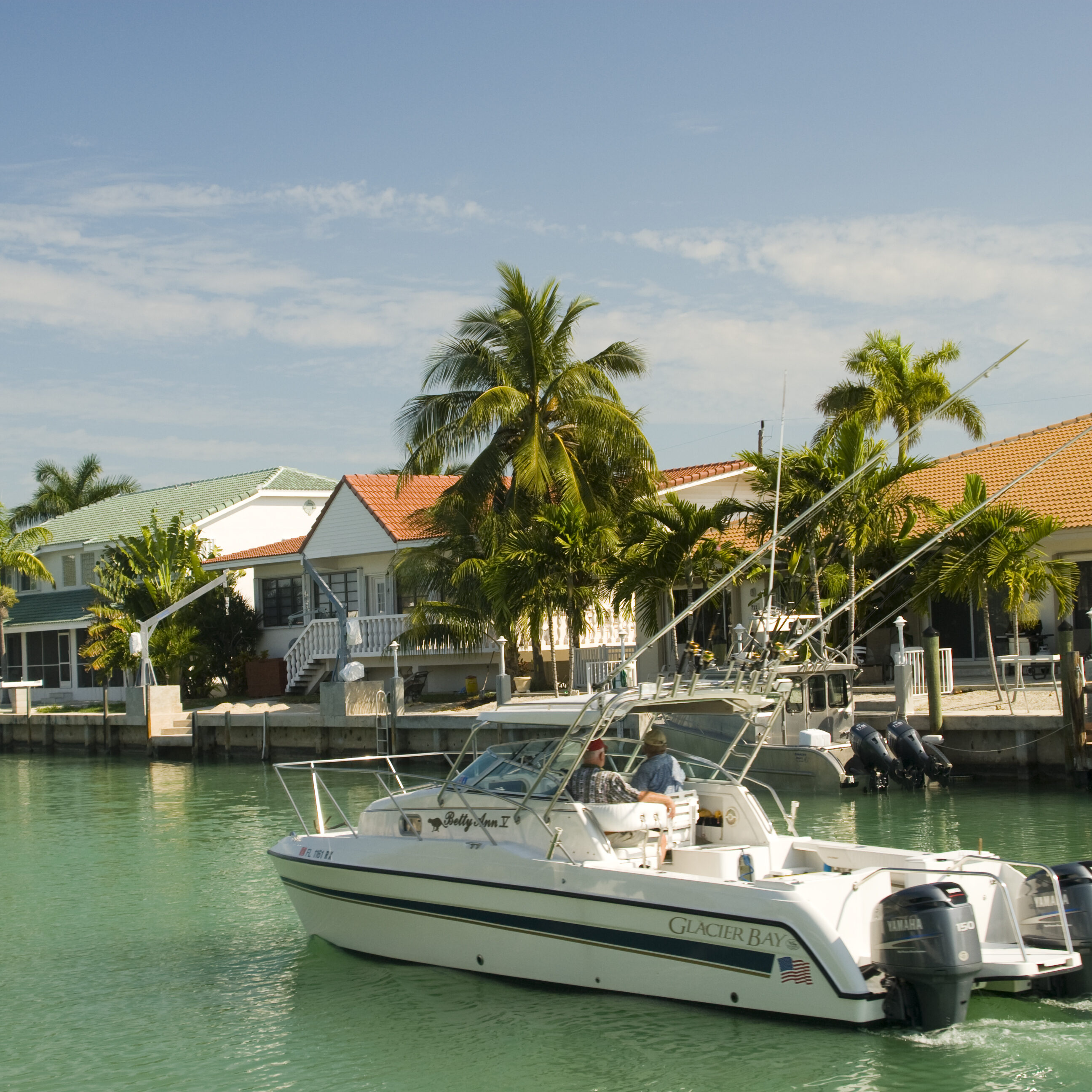 editorial leisure boat cruising canal in florida keys by houses