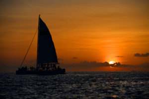 Image of a sunset with sail boat in the foreground