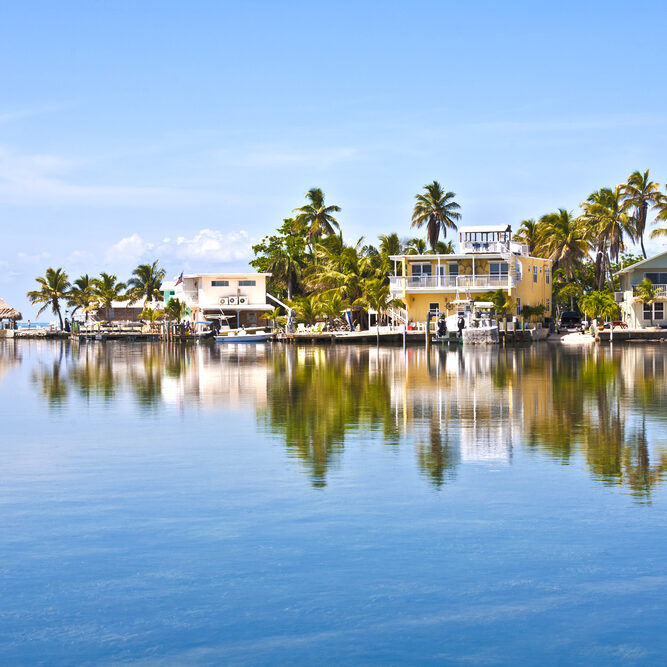 picture of calm water looking towards homes and boats on the water
